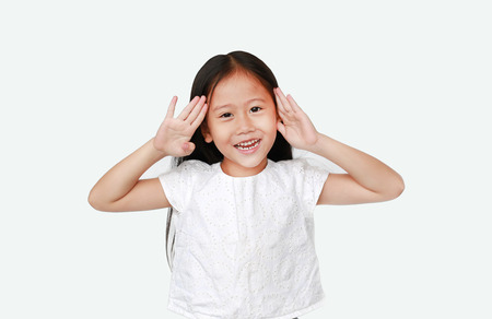 Happy little Asian child girl gestures playing peekaboo over white background. Kid posture open hands from eyes with smile. 免版税图像