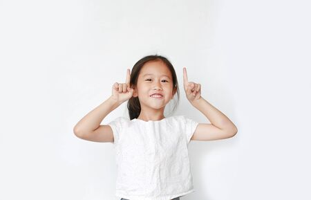 Cheerful little Asian child girl raised two forefinger to cheer isolated on white background. Cheerful emotion concept.