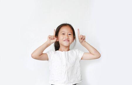 Fröhliches kleines asiatisches Kindermädchen hob zwei Zeigefinger, um isoliert auf weißem Hintergrund zuzujubeln. Fröhliches Emotionskonzept.