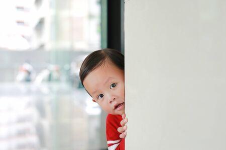 Adorable little boy hide behind a corner room. Baby playing peekaboo game indoor.