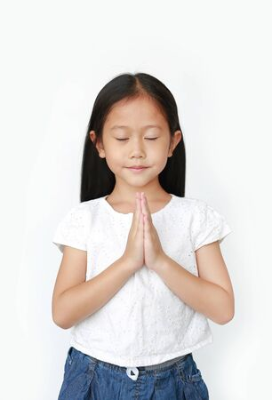 Closed eyes little asian kid girl praying isolated on white background with copy space. Sawasdee is meaning hello.