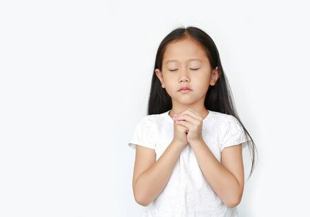 Close eyes beautiful little asian child girl praying isolated on white background. Spirituality and religion.