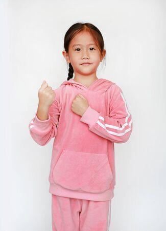 Adorable niña asiática en chándal rosa o tela deportiva con expresión de lucha aislada sobre fondo blanco. Retrato de medio cuerpo de niña niño. Concepto de confianza. Foto de archivo