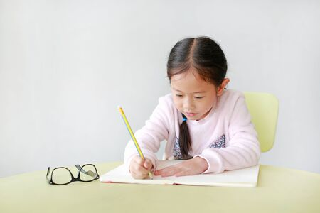 Portrait of smiling little Asian girl writes in a book or notebook with pencil on table in classroom against white background.