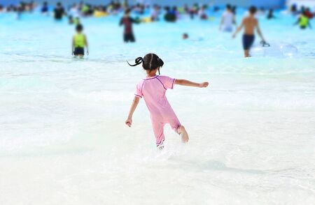 Little Asian child girl enjoys and running into big Swimming pool outdoor on holidays. Rear view children having fun. Stockfoto