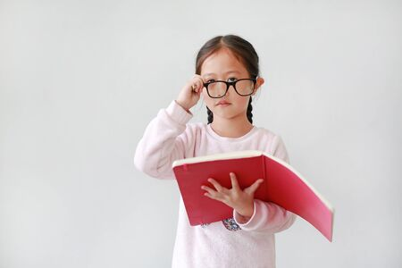 Portrait of little Asian Schoolgirl take off glasses and holding notebook with pencil on white background. 版權商用圖片