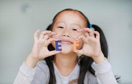 Adorable niña asiática que sostiene el texto del alfabeto EF (funciones ejecutivas) en su rostro. Concepto de educación y desarrollo.