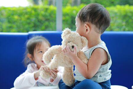 Asian sister scrambling teddy bear with her little brother.