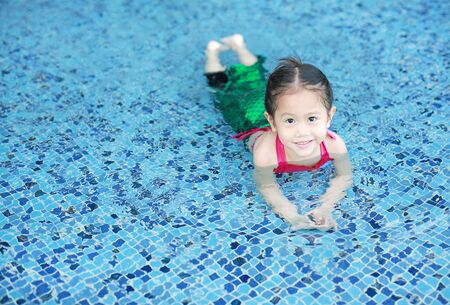 Smiling little Asian child girl in a mermaid suit playing poolside with looking camera.