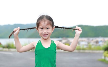 Happy little Asian child girl in mountain field holding her pigtails hair with looking at camera.
