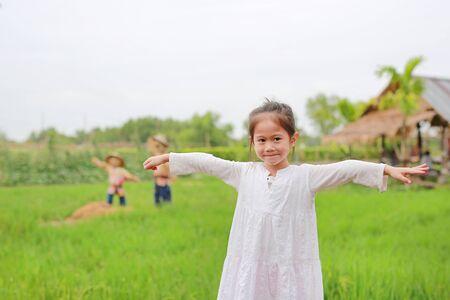 Niña asiática linda Estire los brazos en los campos de arroz verde fresco. Foto de archivo