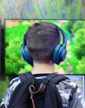 Rear of boy gamer with headphones playing competitive gaming.