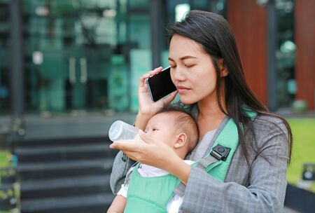 Close up business woman talking by telephone with carrying infant baby boy and holding her child's milk bottle.