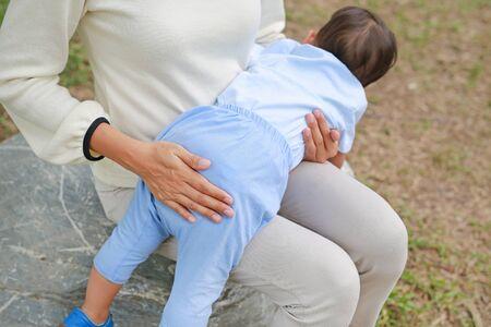 Mutter schlug ihr Kind im Freien. Mutter bestraft Sohn, indem sie mit der Hand schlägt. Konzept der Gewalt in der Familie. Standard-Bild