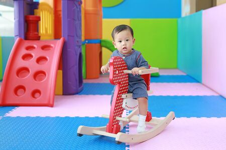 Happy baby boy playing horse on playground, wooden rocking.