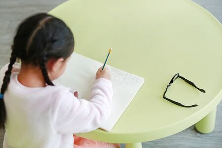 Rear view of little child writes ABC in a book or notebook with pencil on table in classroom against white background. Stock fotó