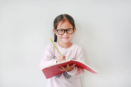 Happy little Asian child girl wearing eyeglasses and hold a book and write with pencil on white background.
