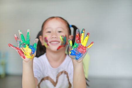 Happy little Asian girl with her colorful hands and cheek painted in the children room. Focus at baby hands. Фото со стока - 134638994