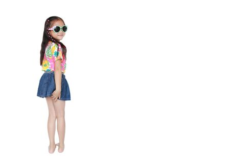 Happy little Asian kid girl wearing a flowers summer dress and sunglasses isolated on white background with copy space. Summer fashion kid concept.