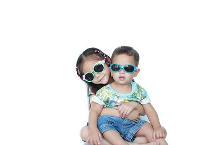 Portrait little Asian sister embracing little brother wearing a flowers summer dress and sunglasses isolated on white background. Summer and fashion concept.