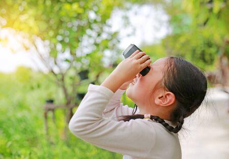Kid girl kid regardant vers l'avenir avec des jumelles dans les champs de la nature. Concept d'exploration et d'aventure.