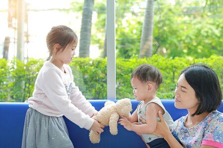 Ältere asiatische Schwester gibt dem jüngeren Bruder Teddybärenspielzeug, während die Mutter auf ihre Kinder aufpasst. Familienbeziehungskonzept. Standard-Bild