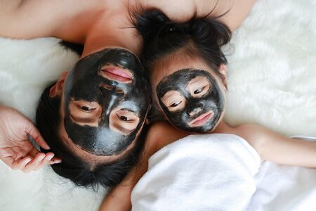 Young woman and child girl in black peeling face mask, beauty concept. Фото со стока