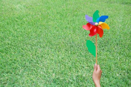 Hand holding colorful pinwheel in the garden