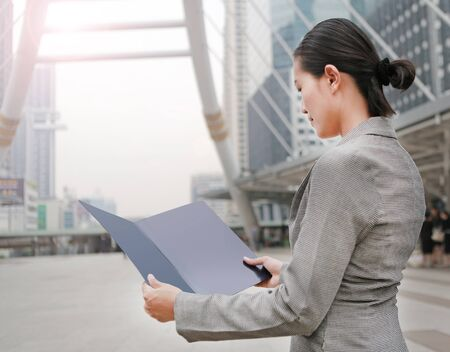 Beautiful business woman open cover sheet in her hands outdoors.