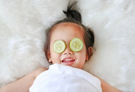 Cute little Child girl with a slice of cucumber in her eye, concept for skin care. Фото со стока