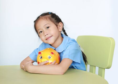 Portrait of Asian little girl in school uniform sitting on table and hugging yellow piggy bank on white background. Schoolgirl with Money saving concept. Фото со стока - 135456243