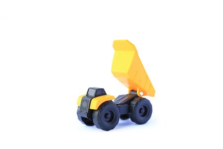 The yellow toy car Heavy truck isolated on white background. Children's tractor toy. Wheel loader construction car model. Stock Photo