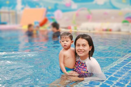 Asian mother and baby boy swimming in pool training with happiness. Фото со стока - 135456338