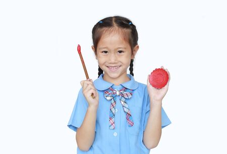 Cheerful Asian little girl in school uniform holding Red dipped paintbrush and palette with looking at camera isolated over white background. Фото со стока - 135456290