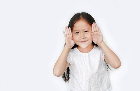 Happy little child girl gestures playing peekaboo over white background with copy space. Kid posture open hands from eyes with smile. Фото со стока - 135456148