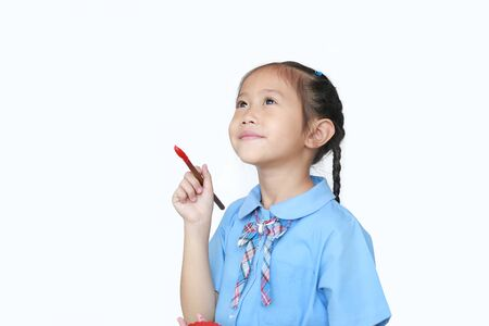 Asian little child girl in school uniform holding Red dipped paintbrush thinking of drawing something over white background. Фото со стока - 135456313