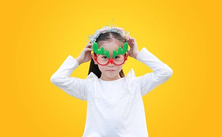 Adorable little Asian girl reindeer putting on the head of multi-color paper spray on yellow background. A moment of celebration concept. Фото со стока - 135456253