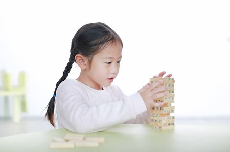 Cute little Asian child girl playing wood blocks tower game for Brain and Physical development skill in a classroom. Focus at children face. Kid imagination and learning concept. Фото со стока - 135456297