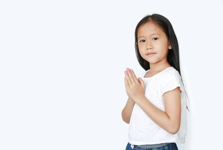 Smiling little girl praying isolated on white background with copy space. Sawasdee is meaning hello. 스톡 콘텐츠