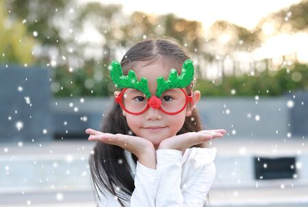 Close-up face of smiling little girl reindeer with floating snow in winter season outdoor. Фото со стока - 135456264