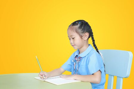 Asian little girl in school uniform writing on notebook at desk isolated over yellow background. Schoolgirl and Education concept. Фото со стока - 135456344