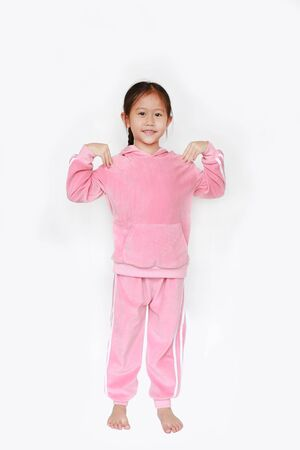 Adorable little Asian child girl in pink tracksuit or sport cloth doing exercises over white background. Фото со стока - 135456205