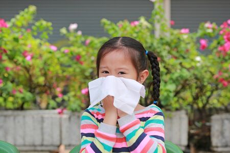 Portrait little Asian girl blowing her nose with tissue paper sitting outdoor. Фото со стока - 135456298