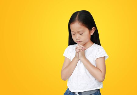 Close eyes beautiful little asian child girl praying isolated on yellow background with copy space. Spirituality and religion concept. 스톡 콘텐츠
