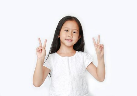 Smiling little kid girl showing two finger gesture as sign as fighting isolated over white background. Фото со стока - 135456173