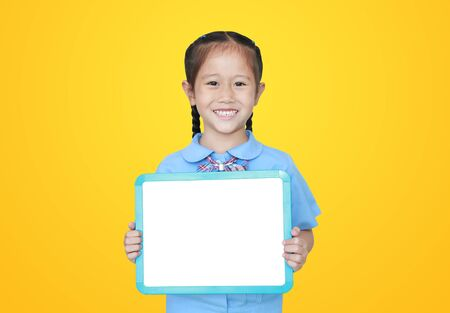 Cheerful Asian little girl in school uniform holding blank white blackboard isolated on yellow background. Student and Education concept. Фото со стока - 135456227