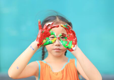 Portrait of Asian little girl looking through her colorful hands painted. Focus at baby hands. Kid with hands glasses in front of her eyes. Фото со стока - 135458642
