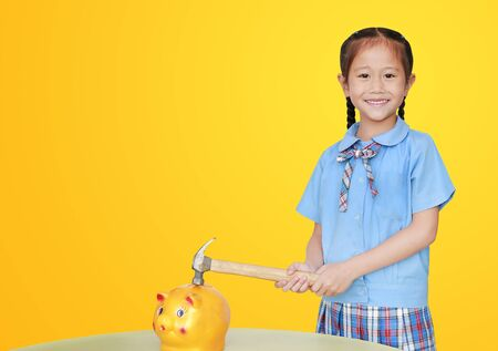 Smiling little asian girl in school uniform preparing to break the piggy bank with a hammer on yellow background at table. Schoolgirl with Money saving concept. Фото со стока - 135456105