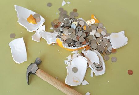 Broken piggy bank with hammer and coins on table.