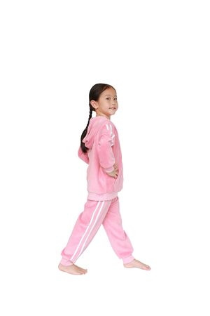 Portrait of smiling little Asian kid girl in pink tracksuit or sport cloth doing exercises isolated on white background. Фото со стока - 135456317